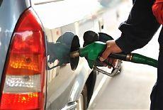Автозаправщик заливает топливо в бак автомобиля