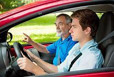 Начинающий водитель за рулем, рядом с инструктором по вождению