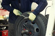 Профессиональный автомеханик выполняет балансировку колеса.