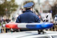 Сотрудник дорожно-патрульной службы с жезлом в руке, на улице рядом с полицейской машиной с мигалкой.