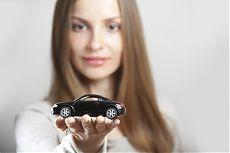 Женщина, держащая в руках модель автомобиля.