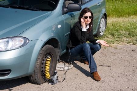 Взволнованная женщина возле неисправного автомобиля звонит в службу техпомощи на дорогах.