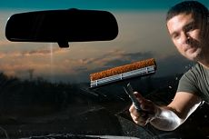 Взрослый мужчина чистит лобовое стекло своего автомобиля.
