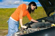 Девушка смотрит на двигатель под капотом своего автомобиля.