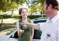 Молодая девушка получает ключи от машины при покупке подержанного автомобиля.