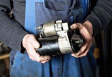 Автомеханик ремонтирует стартер автомобиля ВАЗ