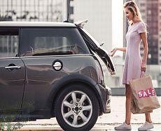 Девушка складывает покупки в багажник авто