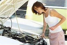 Девушка проверяет уровень масла в двигателе своего автомобиля